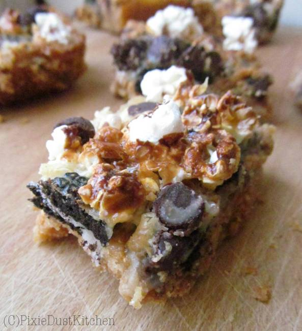 Kitchen Sink Seven Layer Bars... everything but the kitchen sink! A graham cracker crust, with Peanut butter, chocolate chips, Oreo cookies, popcorn, and marshmallow bits, all covered with Sweetened condensed milk. Everything but the kitchen sink... and the perfect way to clean out your cupboards!